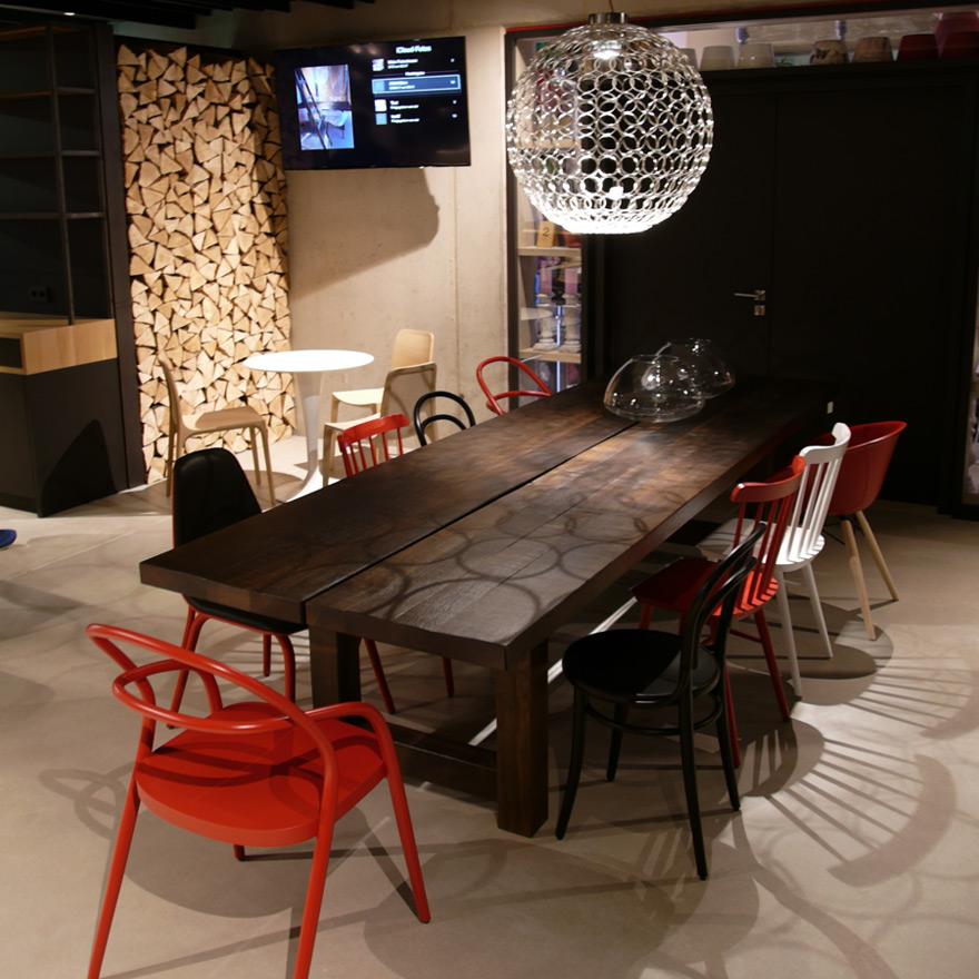 dunkler Massivholztisch mit Designerstühlen